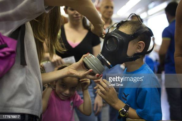 An Israeli woman shows her children how to put on a gas mask as they pick their gas masks at a distribution center on August 26 2013 in Tel Aviv...