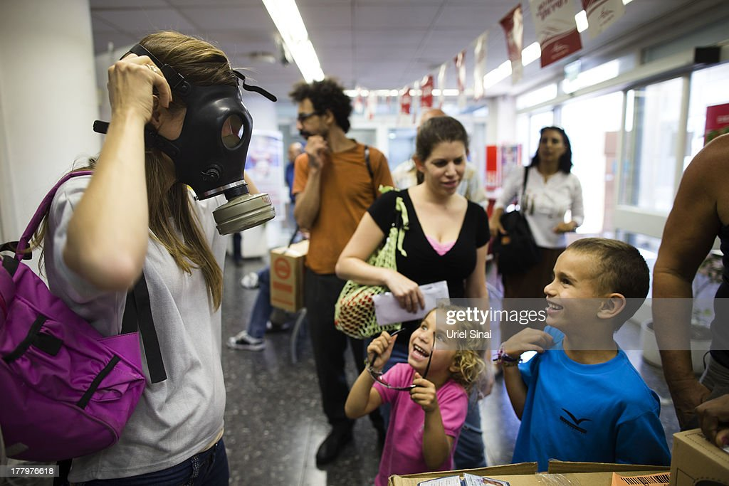 An Israeli woman shows her children how to put on a gas mask as they pick their gas masks at a distribution center on August 26, 2013 in Tel Aviv, Israel. Israel keeps distributing gas masks to its civilian population as tension rises in Israel amid international talks of a military intervension In Syria.