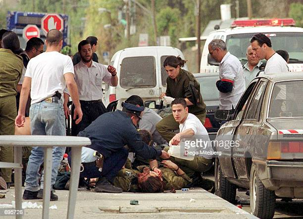 An Israeli woman soldier is treated for her wounds February 10 2002 after two Palestinian gunmen opened fire into a group of Israelis outside the...