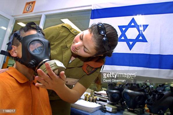 An Israeli woman soldier measures a Jewish youth for a gas mask September 23 2001 at a distribution center in a Jerusalem shopping mall Israelis are...
