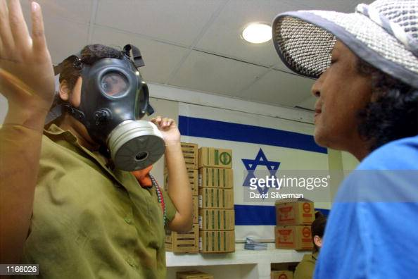 An Israeli woman soldier shows a Jewish woman how to use a gas mask September 23 2001 at a distribution center in a Jerusalem shopping mall Israelis...