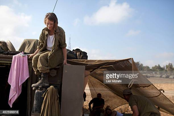 An Israeli woman soldier sits on an Army Armoured Personnel Carrier in a deployment area on July 24 2014 on Israel's border with the Gaza Strip...