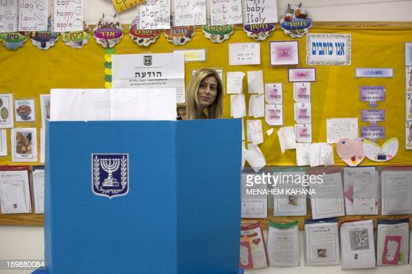 An Israeli woman stands behind a voting booth at a polling station in the Jewish settlement of Har Homa in east Jerusalem on January 22 2013 Voters...