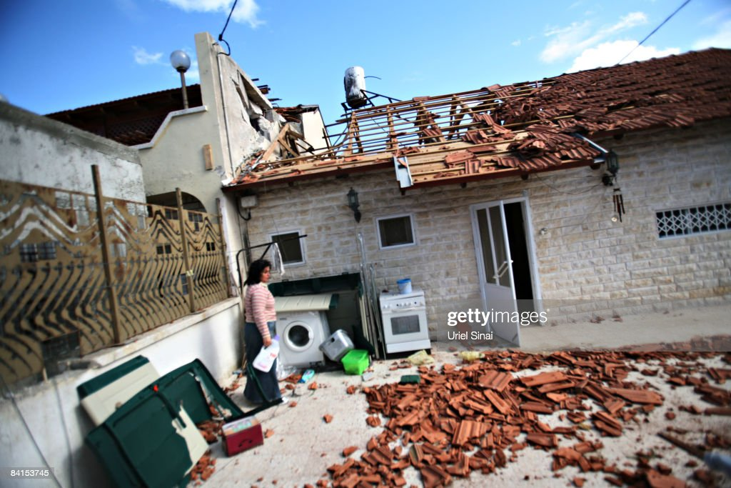 An Israeli woman walks outside her house that was hit by a Palestinian rocket on January 01, 2009.in Sderot, Israel. Israel and the Islamist Hamas both spurned ceasefire calls in a conflict that has killed around 400 Palestinians, 4 Israelis and injured around 1,600.