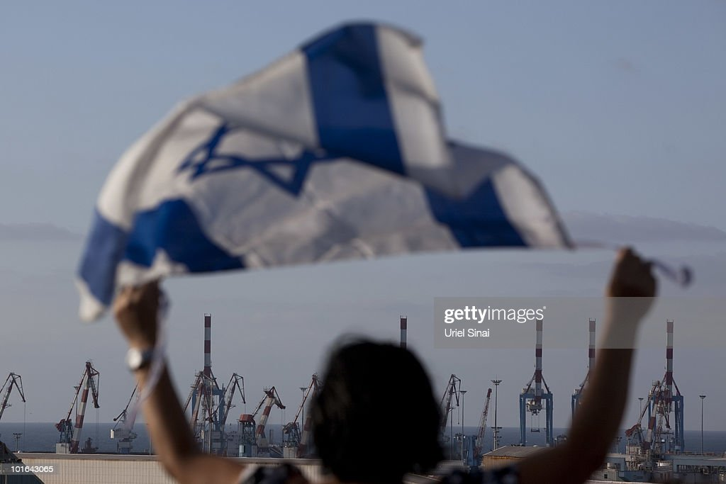 An Israeli woman waves her national flag as the Rachel Corrie aid ship enters the military port of Ashdod in southern Israel after it was intercepted by the Israeli Navy on June 5, 2010, in Ashdod, Israel. Israel, which has faced international criticism over the deadly May 31 raid on a ship carrying humanitarian aid to the Gaza Strip, seized the Rachel Corrie today preventing it from reaching Gaza.