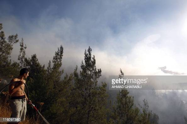 An Israeli youth holds a hose as a firefighting plane sprays its water load over flames to try and extinguish a large forest fire that raged out of...
