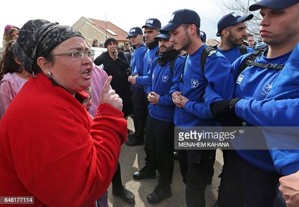 An Israeli youth supporter of settlements argues with Israeli border guards in the settlement of Ofra in the occupied West Bank during an operation...