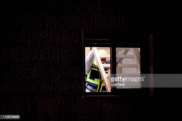 An Israeli Zaka volunteer holds up a bed stained with blood at the Fogel family home March 12 2011 at the Jewish West Bank settlement of Itamar near...