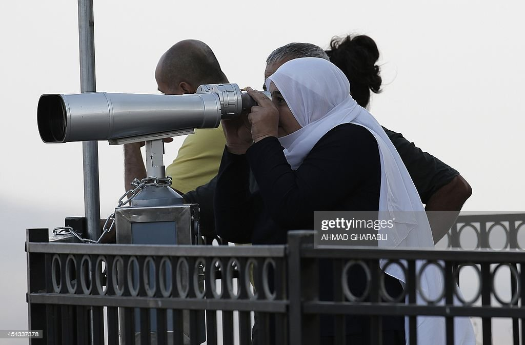 An Israeli-Druze woman looks out from binoculars at smoke rising in the distance caused by fighting between members of the Syrian army loyal to Syrian President Bashar Assad and rebels over the control of the Quneitra border crossing, the only official crossing between Syria and the Israeli-occupied Golan Heights on August 29, 2014. Rebel fighters, including some from Al-Qaeda affiliate Al-Nusra Front, captured the Syrian side of the sole crossing over the armistice line on August 27 in deadly fighting with government troops.