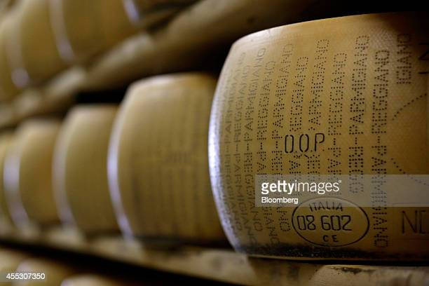An 'Italia' stamp sits on the rind of a ParmigianoReggiano cheese as it sits on a storage rack during the aging process at Coduro cheesemakers in...