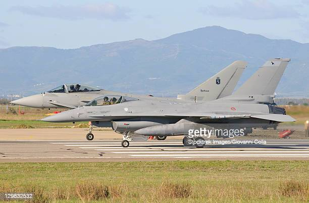 An Italian Air Force Eurofighter 2000 Typhoon and a F-16ADF sit on the flight line at Decimomannu Air Base, Sardinia, Italy, during Exercise Vega 2010.