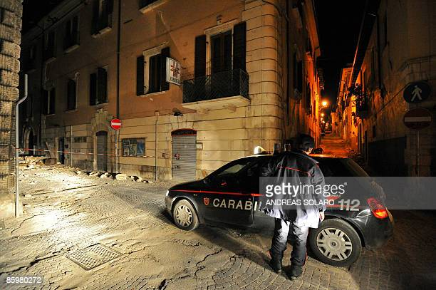 An Italian Carabinieri inspects the streets during a night patrol of the collapsed buildings of the devastated city of L'Aquila on April 14 epicentre...
