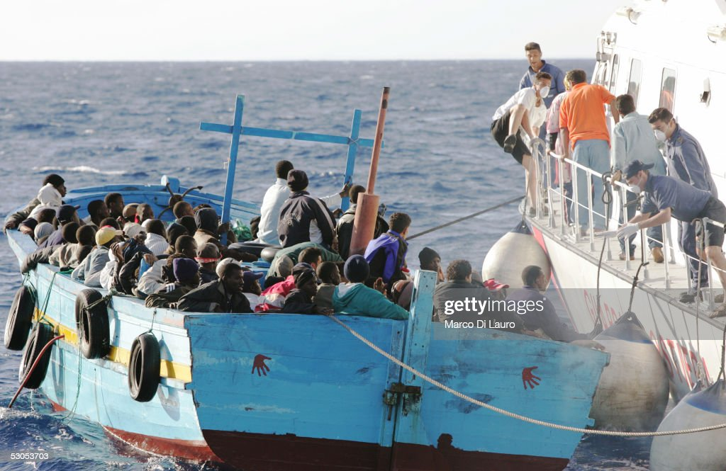 An Italian Coast Guard boat prepares to take illegal immigrants on board June 10 2005 off the coast of Lampedusa Italy Lampedusa Island in the...