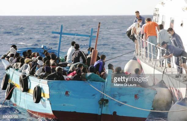 An Italian Coast Guard boat prepares to take illegal immigrants on board June 10 2005 off the coast of Lampedusa Italy Lampedusa Island in the...