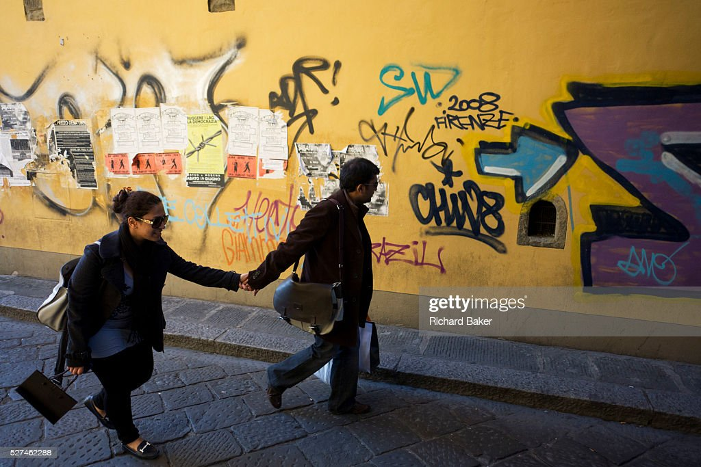 An Italian couple walk along a side street near Florence's Piazza Santa Croce Graffiti lines the far wall and the man partner looks at the writing...
