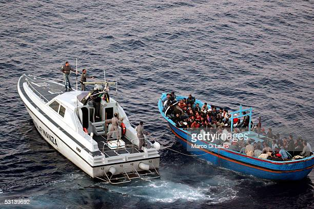 An Italian Custom Police 'Guardia di Finanza' boat approaches a boat loaded with illegal immigrants on June 21 2005 in Lampedusa Italy Tens of...
