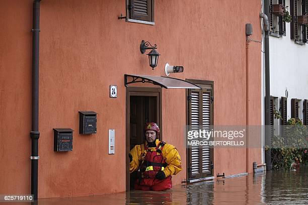 TOPSHOT An Italian fire fighter stands by the entrance of a house during a rescue operation to evacuate people from their home in Moncalieri near...