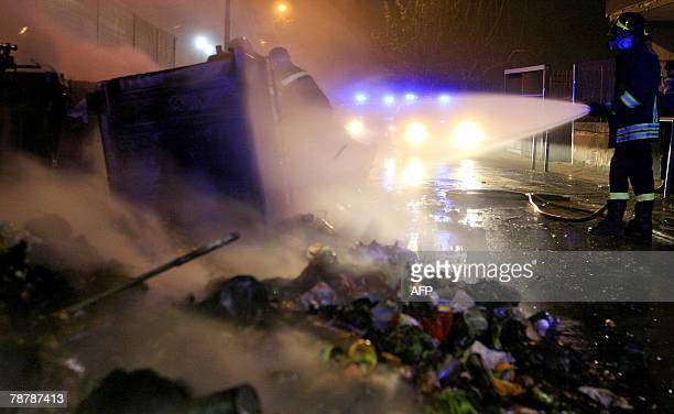 An Italian firefighter sprays water on burning piles of garbage left on the street of a suburb of Naples southern Italy 05 January 2008 The Naples...