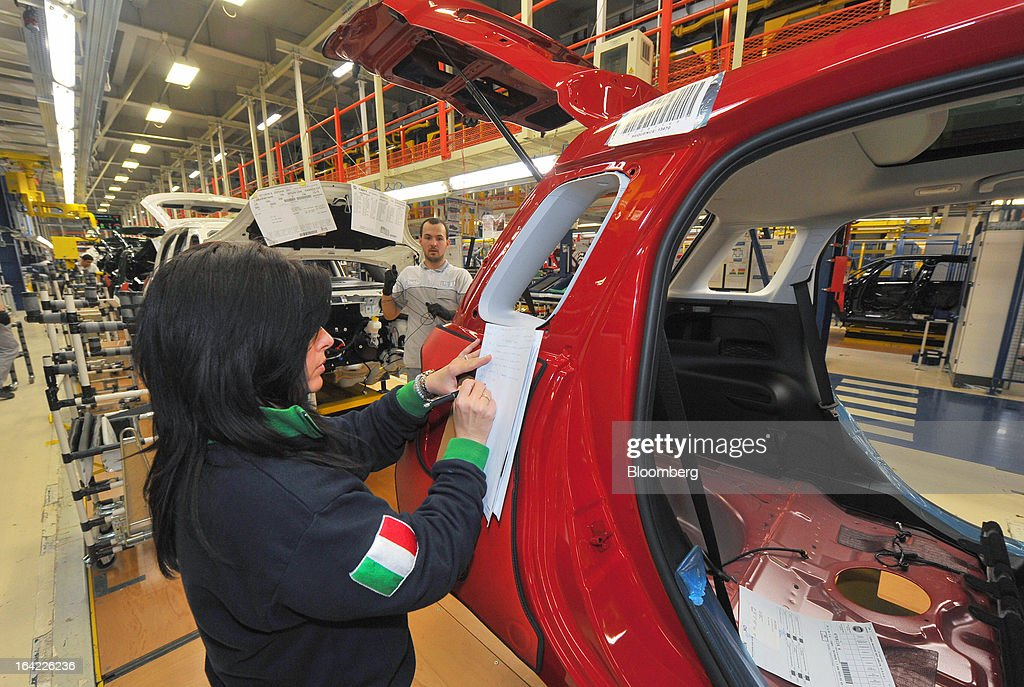 An Italian flag is seen on an employee's jersey as she takes notes while inspecting a Fiat 500L automobile on the production line at the Fiat Automobili Srbija plant in Kragujevac, Serbia, on Wednesday, March 20, 2013. Fiat Automobili Srbija, a joint venture between the government and Italian carmaker Fiat, is Serbia's sole automaker. Photographer: Oliver Bunic/Bloomberg via Getty Images