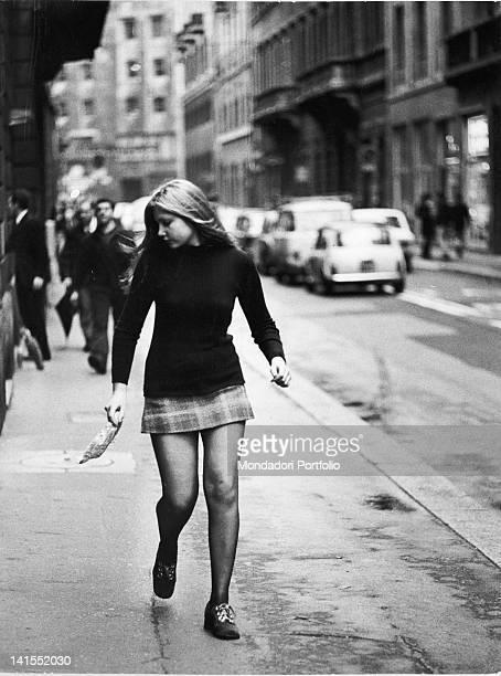 An Italian girl walking down the street in a miniskirt Milan 1971