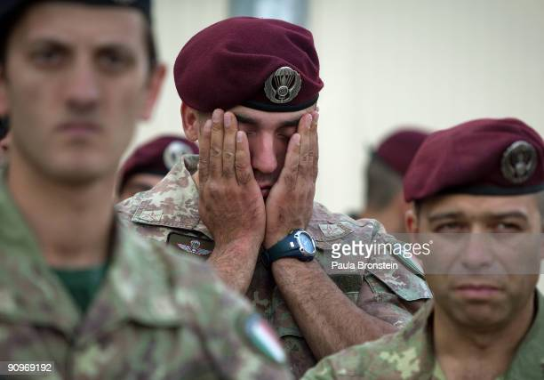 An Italian ISAF soldier gestures during a memorial service for the six soldiers killed after a suicide car bomb hit a military convoy on the main...