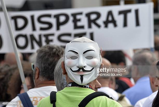 An Italian M5S party' supporter wears a mask as he waits for antiestablishment 5Star Movement party leader Beppe Grillo on May 23 2014 in Rome's...