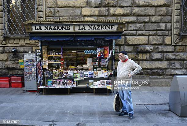An Italian man stands in front of a magazine and newspaper newsstand in Florence Italy