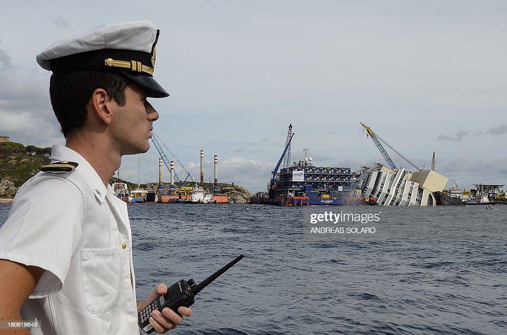 An Italian military Navy officer looks at the wreck of Italy's Costa Concordia cruise ship near the harbour of Giglio Porto on September 15, 2013. Salvage workers will attempt to raise the cruise ship on September 16, 2013, weather permitting, in the largest and most expensive maritime salvage operation in history, so-called 'parbuckling', to rotated the ship by a series of cables and hydraulic machines. Thirty-two people died when the ship, with 4,200 passengers onboard, hit rocks and ran aground off the island of Giglio on January 2012.