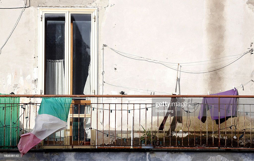 An Italian national flag flies from the balcony of a residential apartment in Vetralla, Italy, on Monday, March 11, 2013. Intesa Sanpaolo SpA and UniCredit SpA are among Italian banks due to report losses for the fourth quarter this week, as the economic contraction meant more clients failed to repay their debts. Photographer: Alessia Pierdomenico/Bloomberg via Getty Images