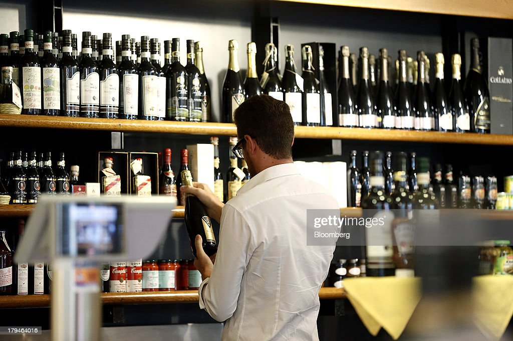 An Italian oenologist checks bottles of Prosecco wine for authenticity at a food and drinks store in Treviso, Italy, on Tuesday, Sept. 3, 2013. Italy's Agriculture Ministry has begun to investigate suspected sales of imitation Prosecco sparkling wine in its native Veneto region. Photographer: Alessia Pierdomenico/Bloomberg via Getty Images
