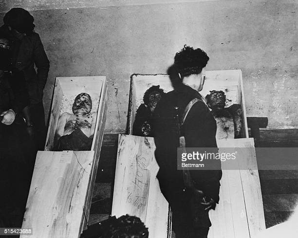 An Italian partisan stands over the bodies of Italian Fascist dictator Benito Mussolini his 33yearold mistress Claretta Petacci and Fascist party...