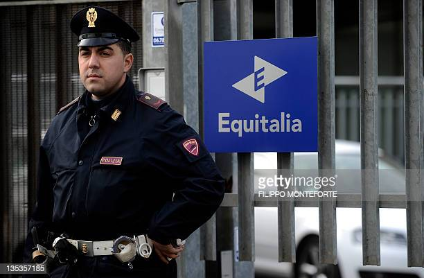 An Italian police officer stands in front of a gate of Equitalia a public company responsible for collecting taxes in Italy after a letter bomb...