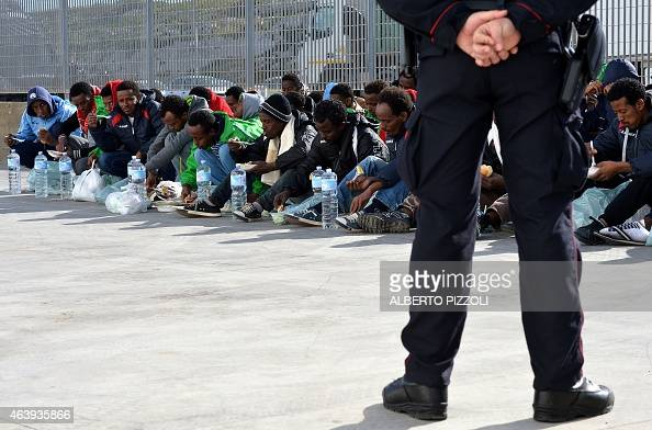 An Italian policeman stands guard as migrants eat while waiting at the port of Lampedusa to board a ferry bound for Porto Empedocle in Sicily on...