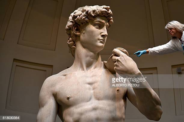 An Italian restorer from the 'friends of Florence association' works on cleaning Michelangelo's David one of the world's most famous statues on...
