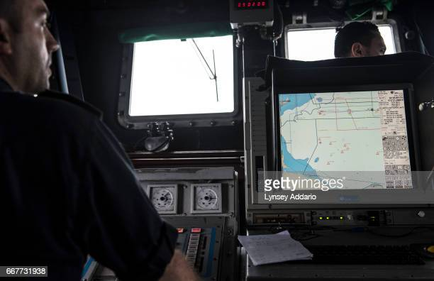 An Italian sailor stands in front of a screen from a radar which shows the possible positions marked with orange triangles of African migrants based...