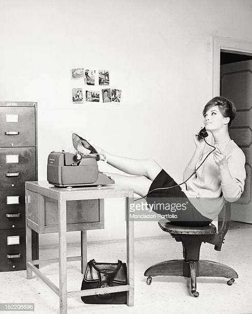 An Italian secretary putting her feet on the desk 1960s