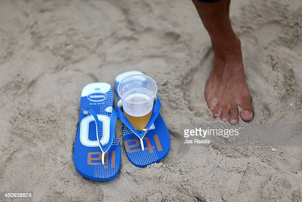 An Italian soccer team fan uses a flip flop to hold a beer cup while watching as his team plays against the Costa Rican team on the screen setup at...