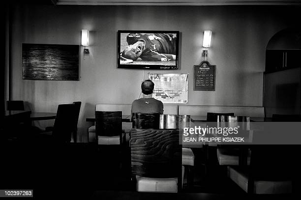 An Italian supporter sits alone in a bar room while watching on TV a broadcast of the 2010 World Cup football match Slovakia versus Italy in the...
