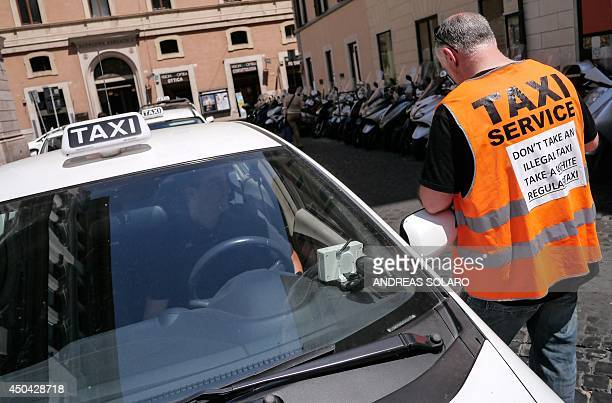 An Italian taxi driver wearing a vest reading 'Don't take an illegal taxi take a white regular taxi' speaks with a colleague during a protest against...