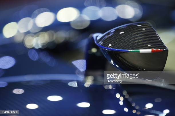 An Italian tricolore detail sits on the tip of a wing mirror of a Pagani Automobili SpA Huayra Roadster luxury automobile as it stands on display on...