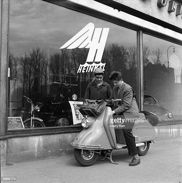 An Italian type Vespa scooter produced by former aircraft manufacturers Heinkel of Stuttgart The vehicle is seen in front of a showroom decorated...