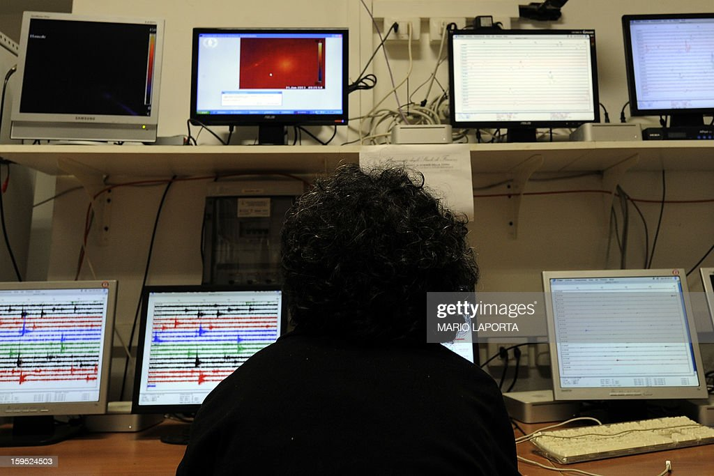 An Italian vulcanoligist looks at screens displaying the Stromboli volcano activity at the C.O.A. (Advanced Operating Centre) in Stromboli island on January 15, 2013. Spectacular lava flows and smoke from an active volcano on the Italian island of Stromboli on Monday sparked fear among inhabitants but geophysicists said the situation was under control. AFP PHOTO / MARIO LAPORTA
