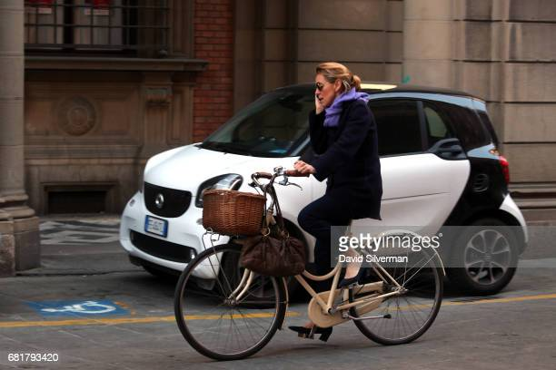 An Italian woman talks on her mobile phone while cycling on March 31 2017 in Bologna Italy Italy's mobile market has one of the highest penetration...