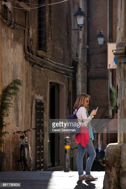 An Italian woman uses her mobile phone in Piazza Santo Stefano on March 31 2017 in Bologna Italy Italy's mobile market has one of the highest...