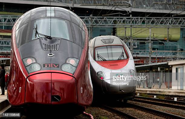 An Italo highspeed train manufactured by Alstom SA and operated by Nuovo Trasport Viaggiatori SpA left stands as a Trenitalia train passes it at...