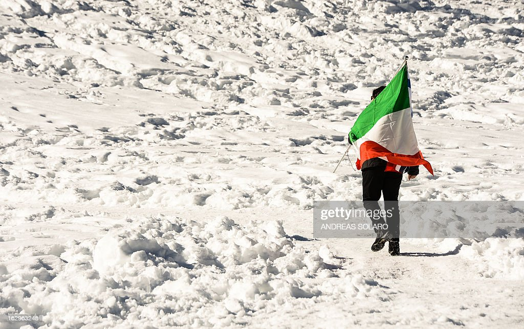 An Italy supporter holds an Italian flag on March 2, 2013 during the Women's Cross Country 30 km Classic race of the FIS Nordic World Ski Championships at Val Di Fiemme Cross Country stadium in Cavalese, northern Italy. AFP PHOTO / ANDREAS SOLARO