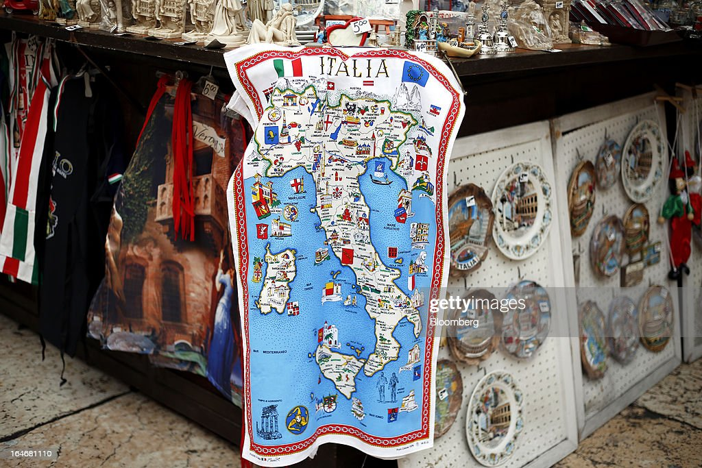 An Italy-themed tea towel sits displayed for sale on a tourist souvenir stall in Piazza delle Erbe in Verona, Italy, on Monday, March 25, 2013. Italy's economy remains mired in its longest recession in two decades and a month-old political impasse threatens to increase sovereign-debt yields and bank funding costs. Photographer Alessia Pierdomenico/Bloomberg via Getty Images