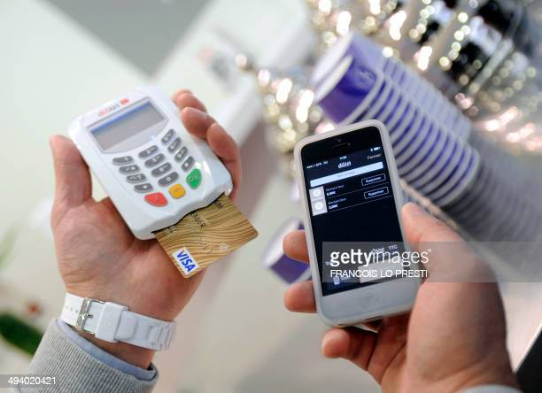 An itinerant merchant uses the new Caisse d'Epargne 'Dilizi' billing system that allows credit card payments thanks to a credit card reader and a...