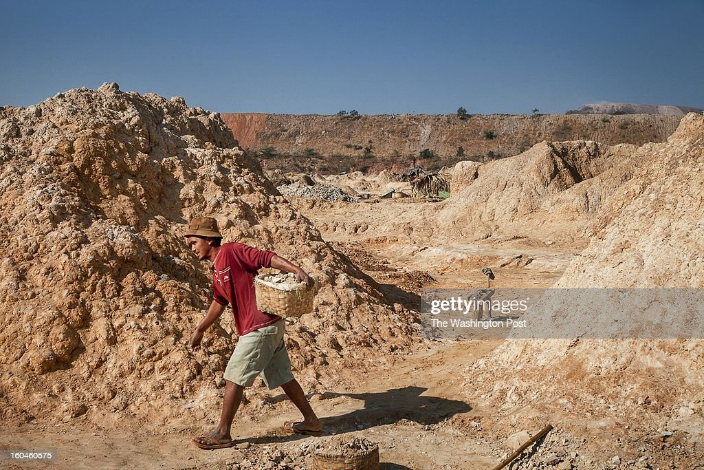 An itinerant worker carries a load of rock to be processed for copper at a private camp on January 26, 2013. The Letpadaung mine would expand on an existing site that has ravaged the landscape since it was started more than fifty years ago.
