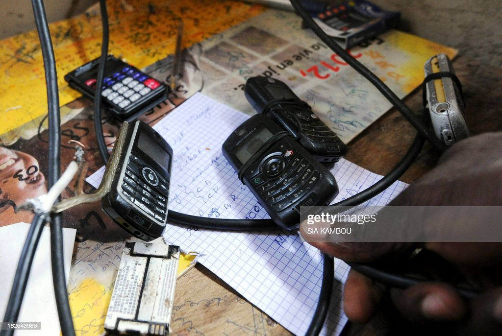 An Ivorian man shows mobile phones with cables linked to antennas installed on the rooftop of a call centre in order to capture a signal in a village without electricity in the sub-prefecture of Seguela, 592 kms from Abidjan, on September 27, 2013. AFP PHOTO/ SIA KAMBOU
